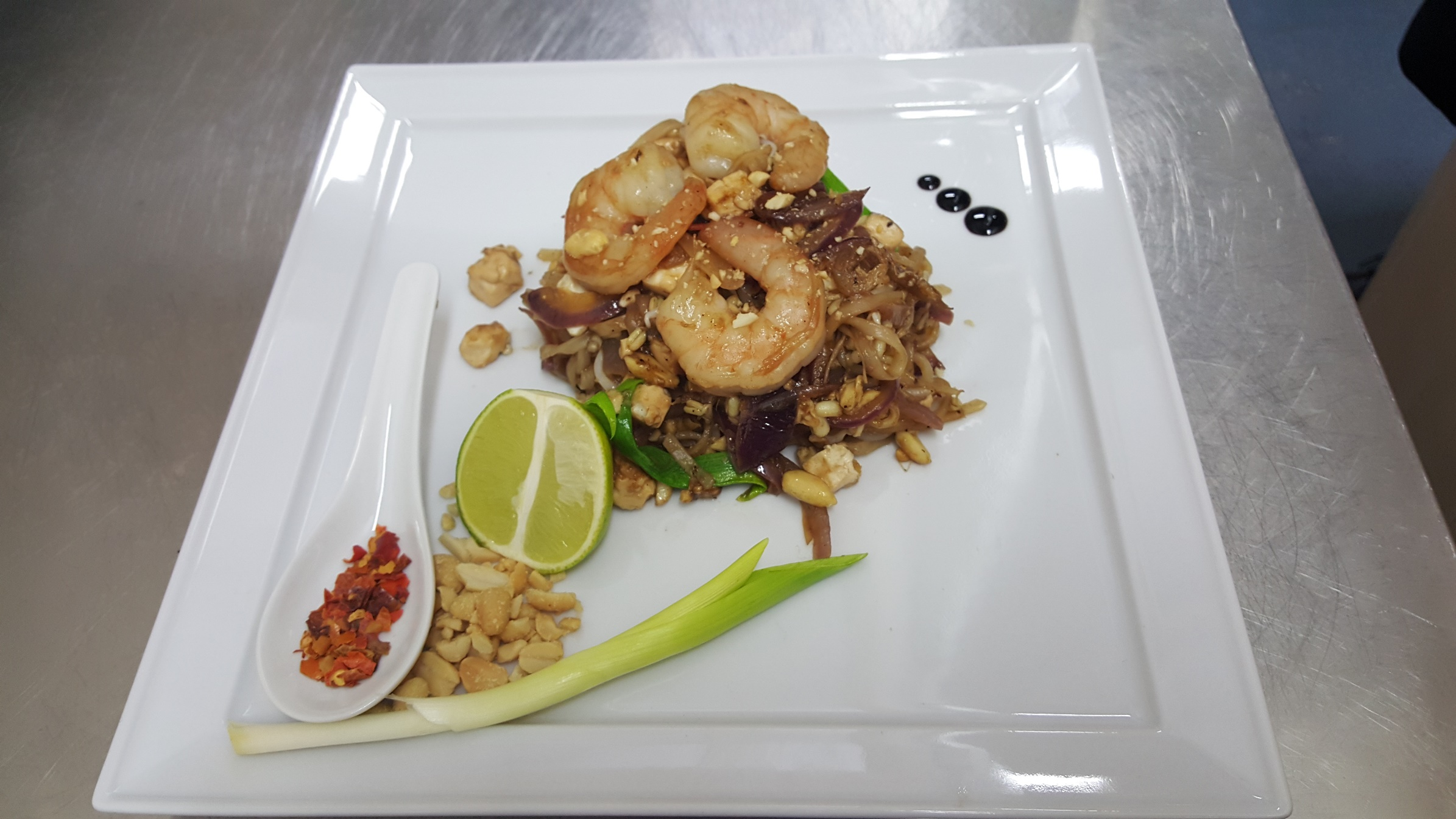 PAD THAI NOODLES - probably most famous and loved recipe of Thai cuisine - jumbo prawns, 	 soya beans sprouts, tofu cheese, egg, red onion in aromatic sauce with piquant sweet flavour